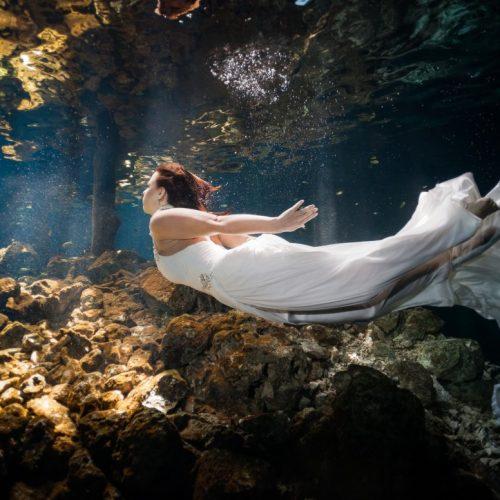 Bride swimming in underwater trash the dress in Mayan Cenote at Riviera Maya