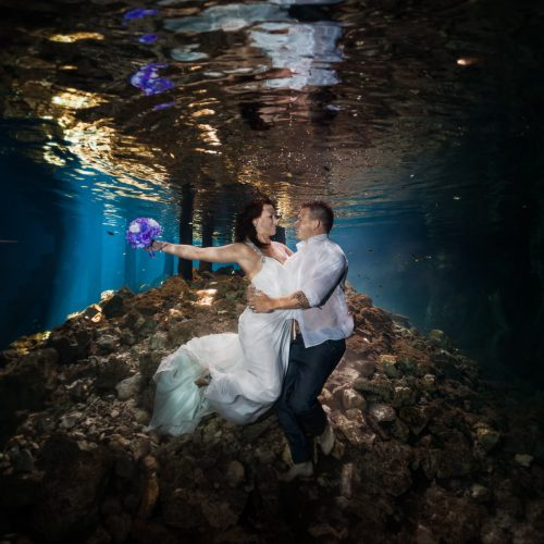 Bride and Groom holding each other in underwater trash the dress in Mayan Cenote at Riviera Maya