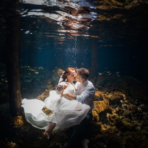 Bride and Groom kissing in underwater trash the dress in Mayan Cenote at Riviera Maya