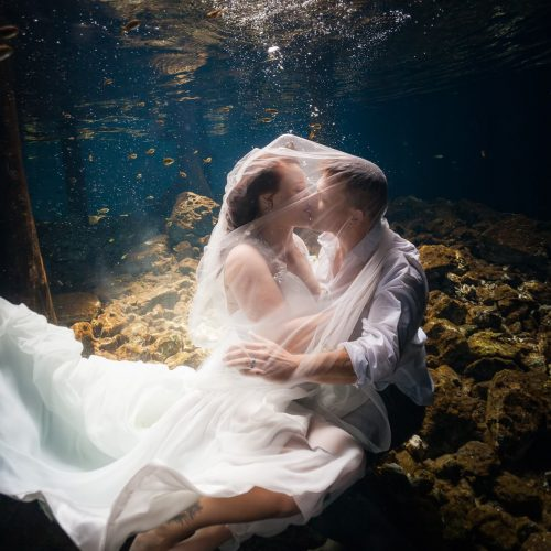 Groom and bride kissing in underwater trash the dress in Mayan Cenote at Riviera Maya