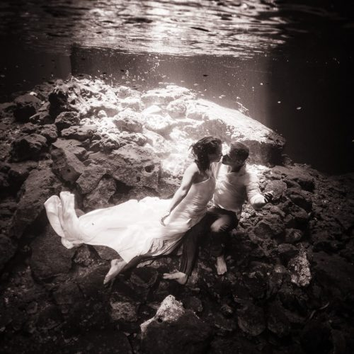 Black and white underwater photography of groom and bride trash the dress in Mayan Cenote at Riviera Maya
