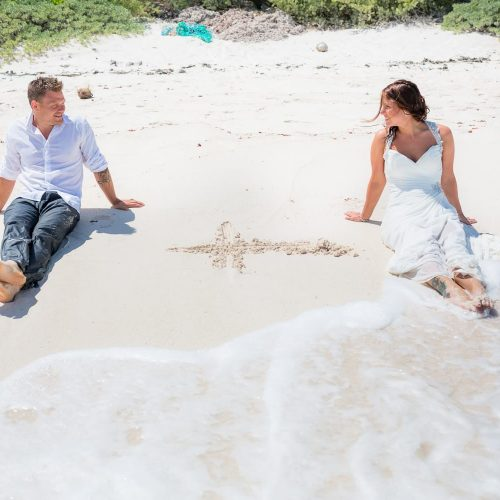 Groom and bride sitting by the shore at trash the dress at Riviera Maya beach