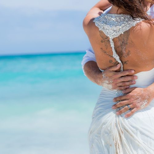 Close up detail to hands of groom on bride's back at trash the dress at Riviera Maya beach