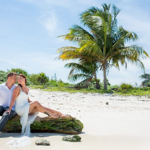 Bride and groom posing for trash the dress photo shoot at Riviera Maya beach