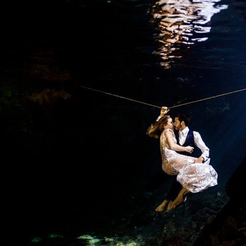 Couple holding in trash the dress photo shoot in Maya Cenote