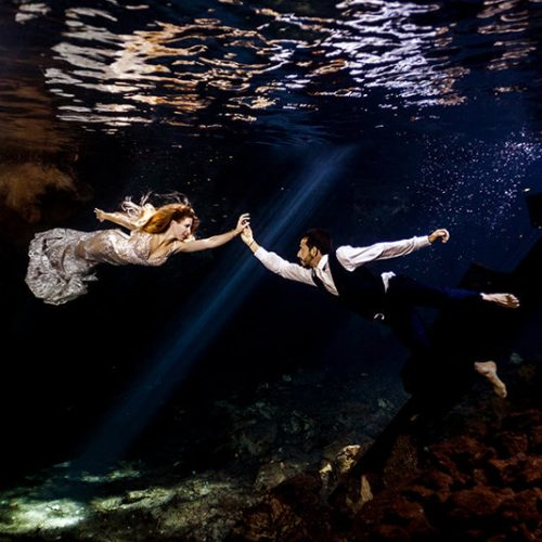 Couple holding hands in underwater photo in Maya Cenote