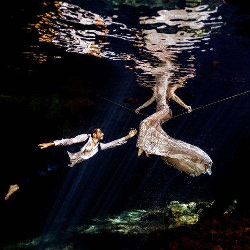 Groom reaching for his bride in underwater photography in Maya Cenote