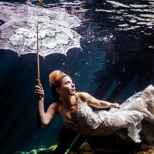 Bride holding an umbrella in underwater portrait in Maya Cenote