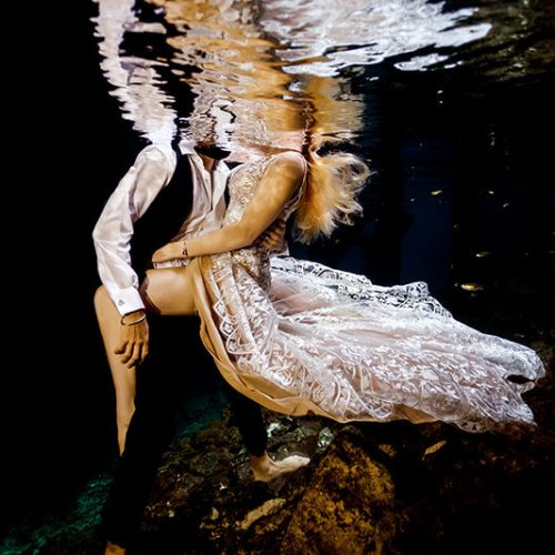 Sexy couple posing in underwater trash the dress in Maya Cenote