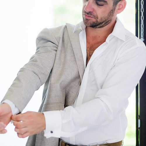 Groom putting on jacket for beach wedding in Mexico
