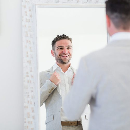 Groom looking at himself in mirror before wedding