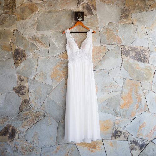 Wedding dress hanging on rock wall in Riviera Maya