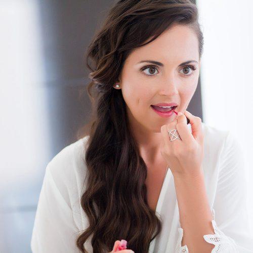 Bride putting on lipstick before her wedding