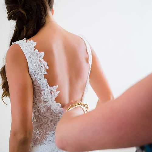 Bride putting on dress before wedding