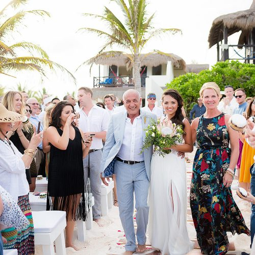Bride walking down beach aisle at wedding in Rivera Maya