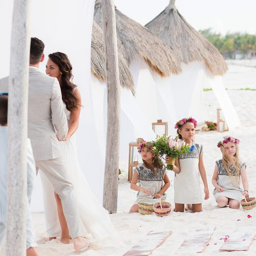 Flower girls watching ceremony at beach wedding