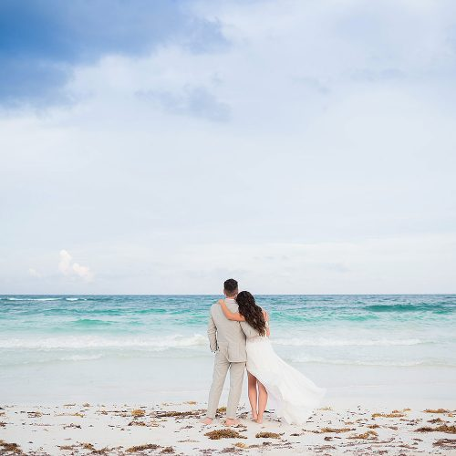 Bride and groom looking at sea in Riviera Maya