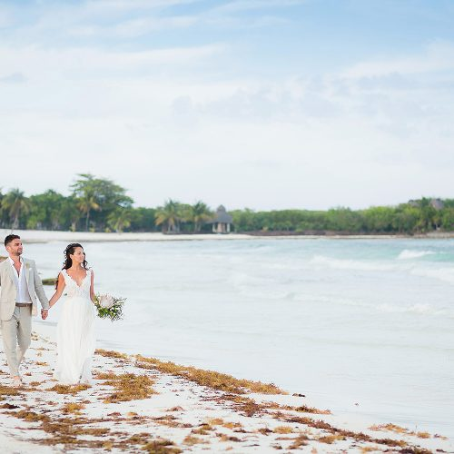 Bride and groom walking on beach in Riviera Maya