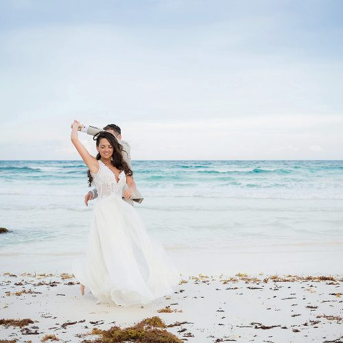 Bride and groom having fun on beach.