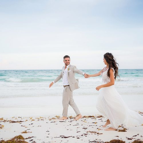 Bride and groom having fun on beach after wedding in Riviera Maya