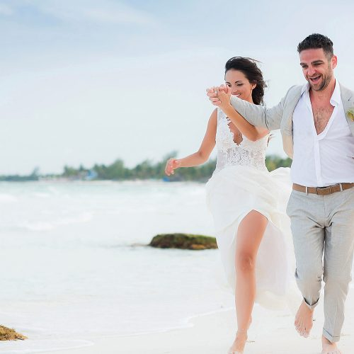 Bride and groom running on beach