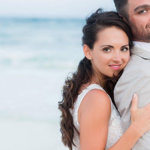 Bride hugging groom on beach.