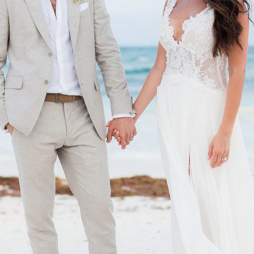 Close up of bride and groom holding hands on beach