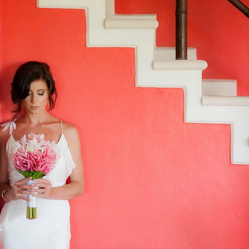 Portrait of bride near stairs before wedding ceremony.