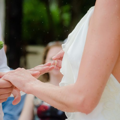 Close up of groom putting on ring at wedding ceremony.