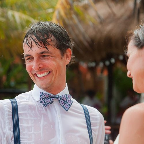 Groom laughing soaking wet at wedding ceremony.
