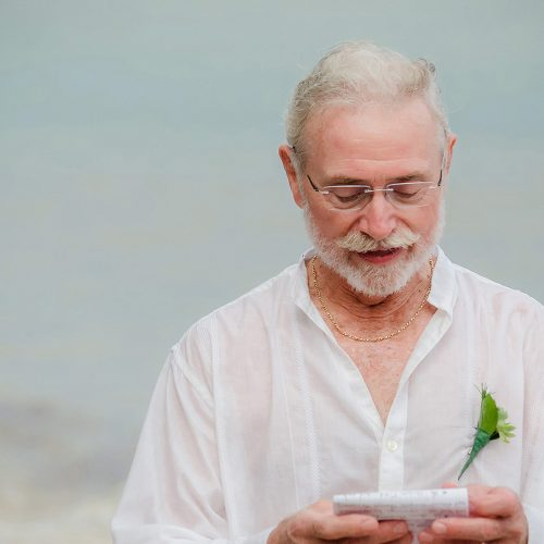 Father giving reading in the rain at wedding in Tulum