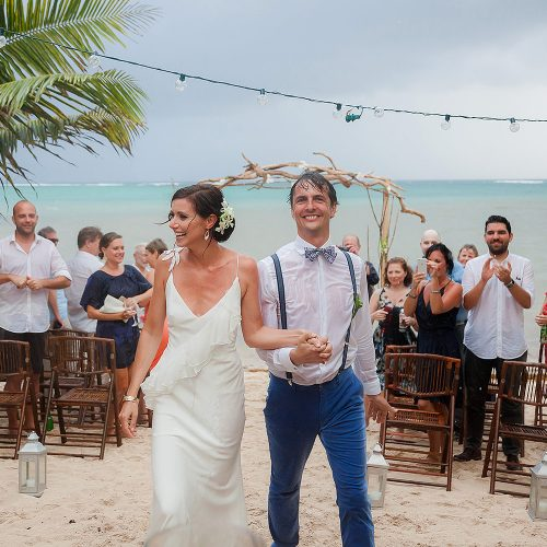 Bride and groom celebrate after wedding ceremony in the rain in Tulum