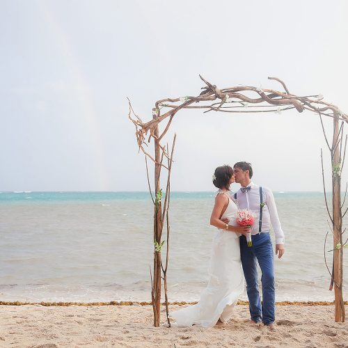 Bride and groom kissing under arch after a rainy ceremony in tulum