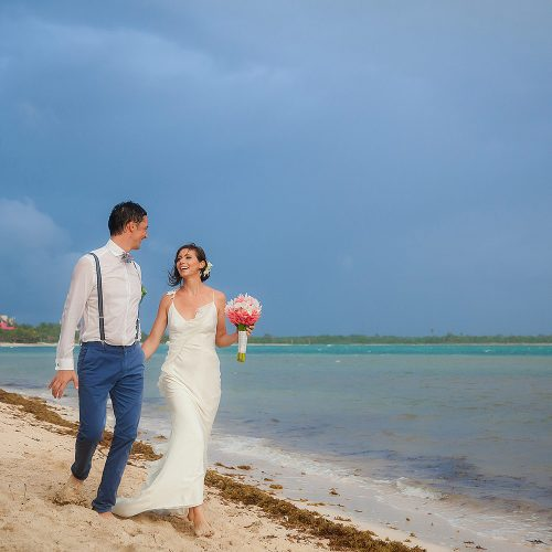 Bride and groom walking on beach in Tulum
