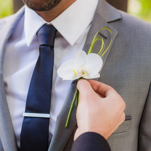 Close up of groom having boutonniere on at wedding