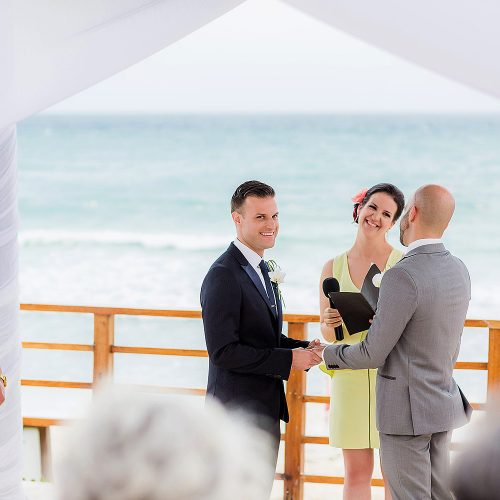 Groom putting on rings at gay wedding.