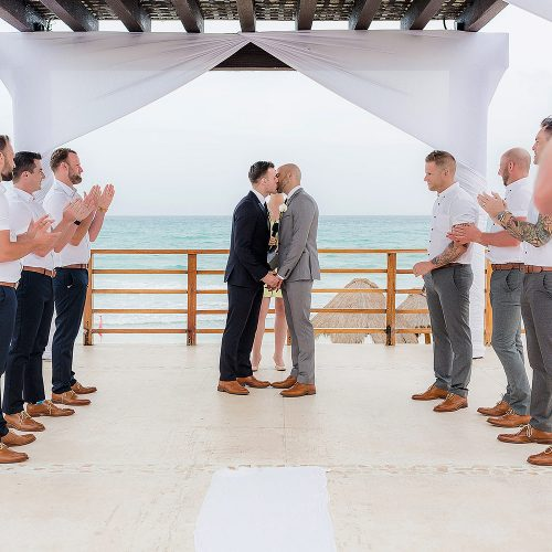 Grooms kissing at gay wedding under pergola at NOW Jade Riviera Cancun resort