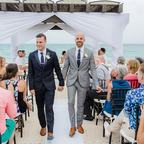 Grooms walking after wedding ceremony at NOW Jade Riviera Cancun resort
