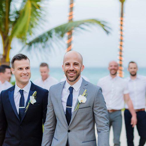 Grooms walking with groomsmen behind in garden at NOW Jade Riviera Cancun