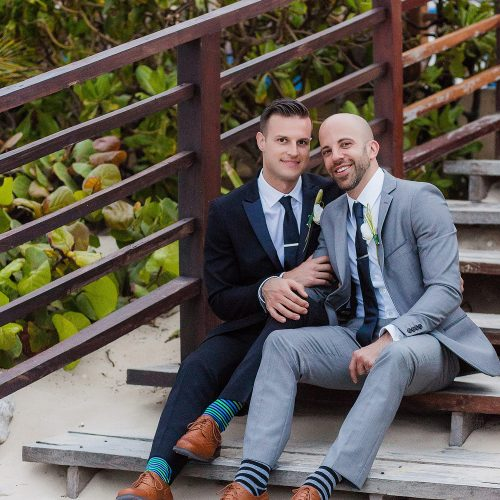 Grooms siting on steps at gay wedding at NOW Jade Riviera Cancun, Mexico