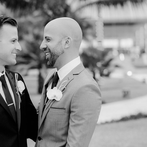 Groomsmen looking at each other at gay wedding