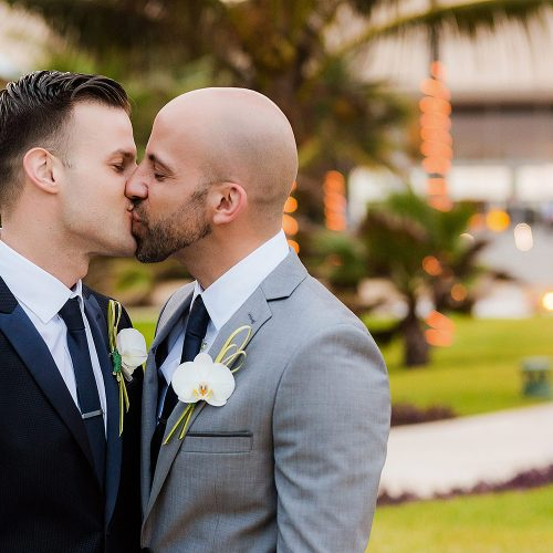 Grooms kissing after gay wedding