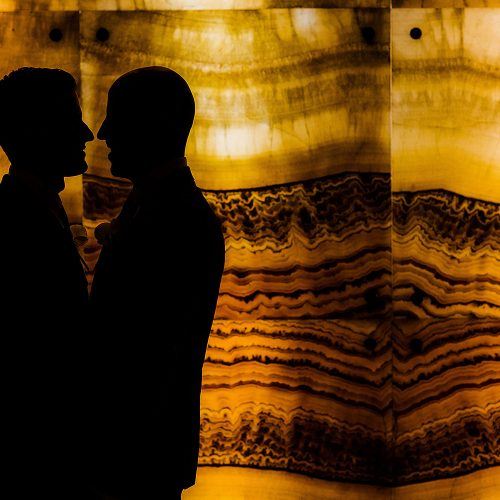 Silhouette photograph of grooms in lobby at NOW Jade Riviera Cancun resort.