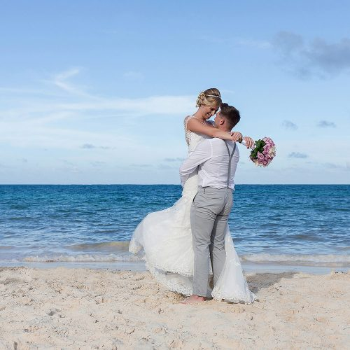 Bride and groom having fun on beach in Cancun