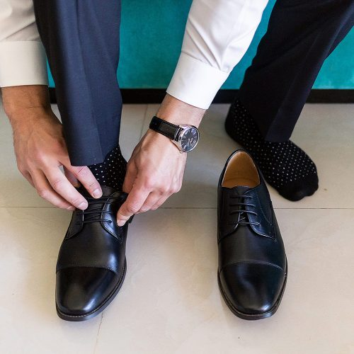 Close up of the groom putting on shoes at NOW Jade resort Cancun