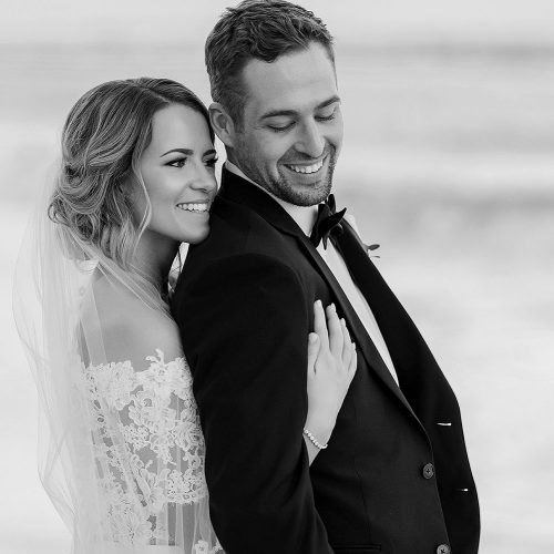 Bride hugging groom from behind on beach at wedding in Cancun | Dean Sanderson Weddings