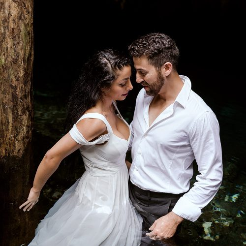 Couple about to kiss in trash the dress in a Mayan Cenote