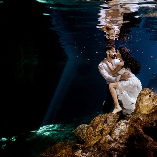 Bride and Groom underwater in wedding outfits at Trash the Dress in Riviera Maya Mexico