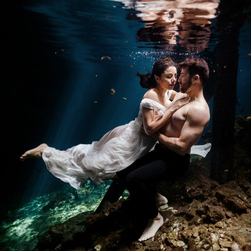 Bride and groom in underwater TTD with shirt off
