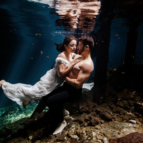 Bride and groom underwater with grooms shirt off in Maya Cenote Trash the dress.